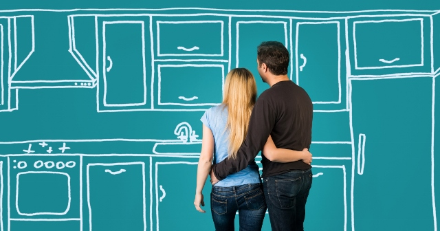 Happy embracing couple planning their home kitchen furnishing renovation. Sketch kitchen drawing.