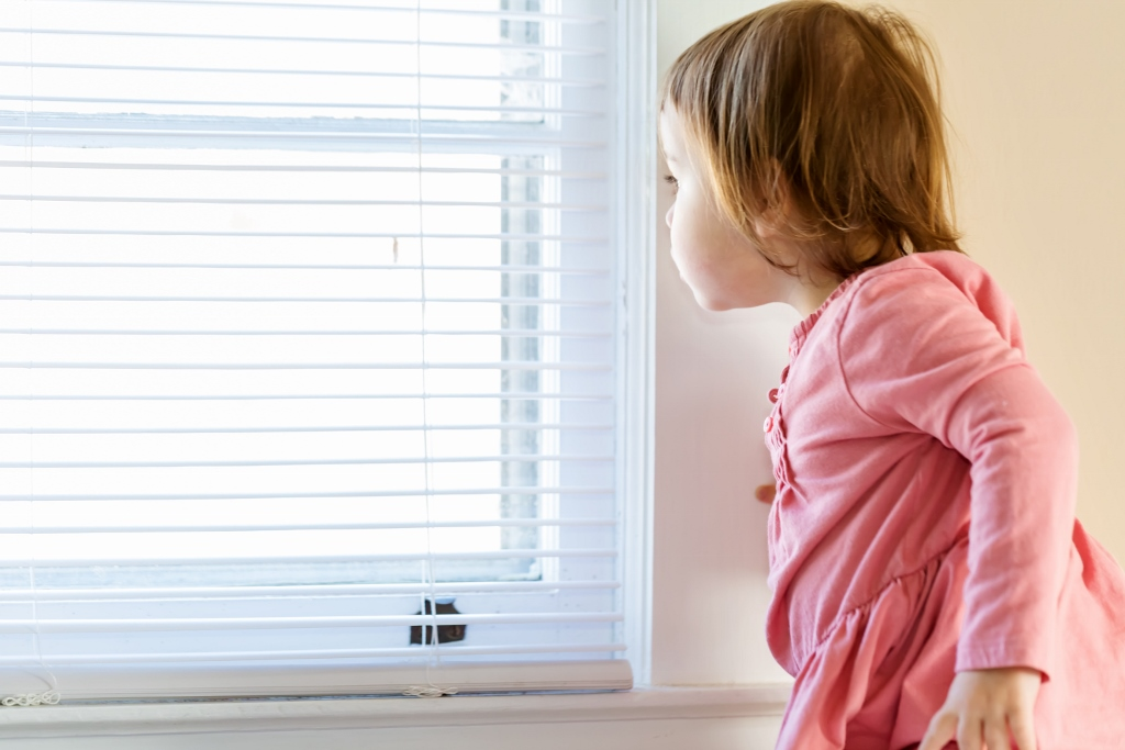 Toddler girl peeking out of the window