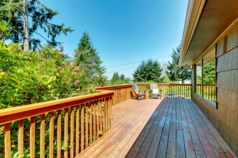 Long Deck, terrace with wood railings and green landscape.